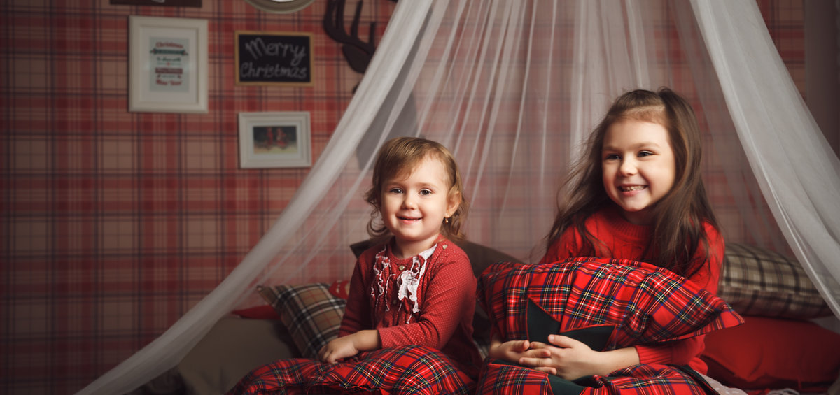 Two little cute girls on bed in scottish style
