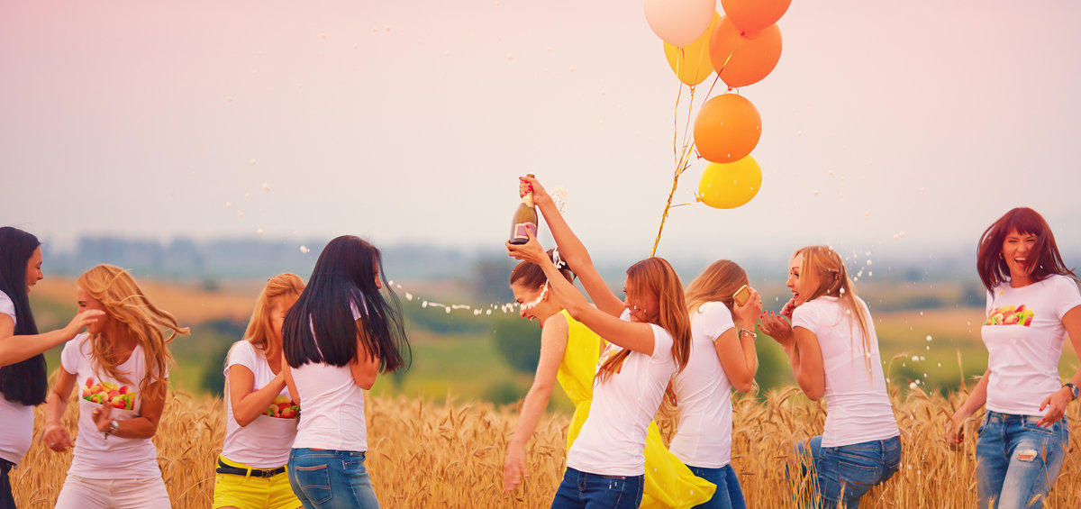 group of happy women with bottle of champagne on summer field