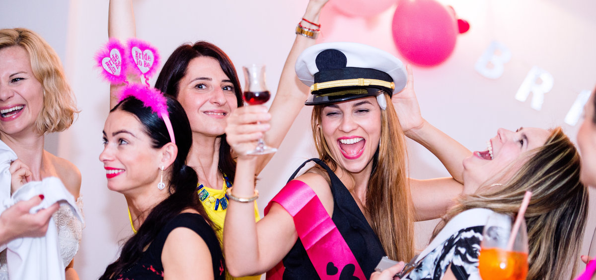 Cheerful bride and bridesmaids celebrating an unforgettable hen party with drinks