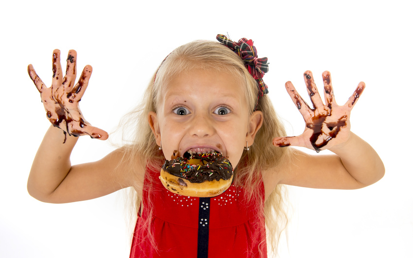 pretty little female child with long blond hair and blue eyes wearing red dress bitting donut mouth showing dirty hands